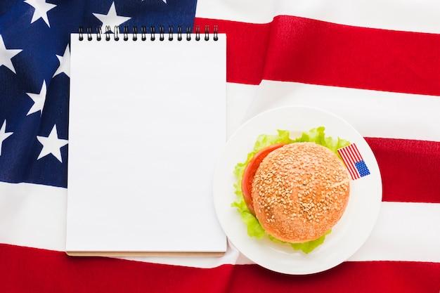 Vista superior del cuaderno con hamburguesa y bandera americana