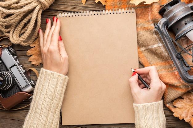 Vista superior del cuaderno con hojas de otoño y cámara