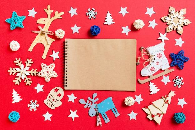Vista superior del cuaderno, juguetes navideños y decoraciones en navidad roja.