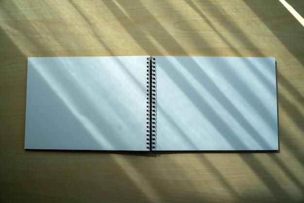 Vista superior del cuaderno liso en blanco fondo del concepto de diseño en blanco para la página del libro de maquetas con cuaderno liso en blanco estacionario