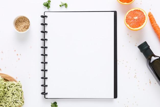 Vista superior del cuaderno de menú en blanco con aceite de oliva y zanahoria