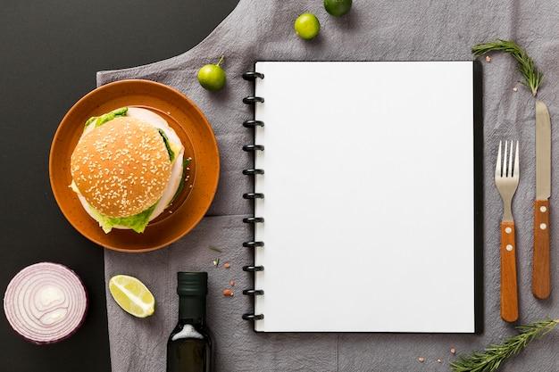 Vista superior del cuaderno de menú en blanco con hamburguesa en placa
