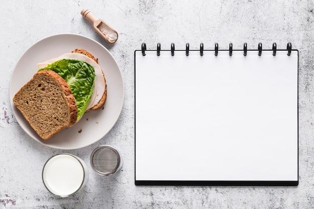 Vista superior del cuaderno de menú en blanco con sandwich
