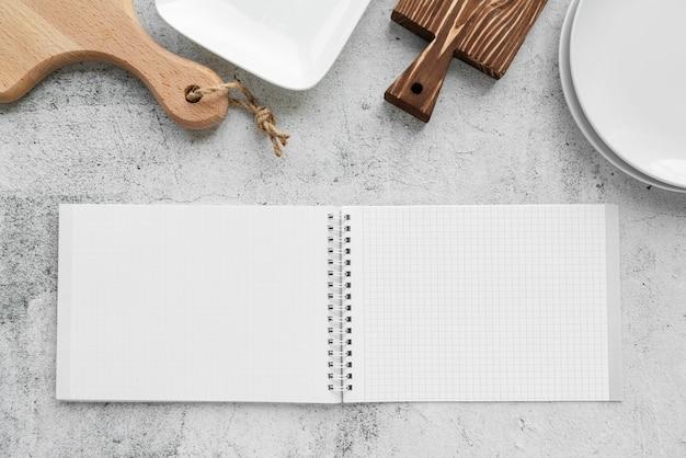 Vista superior del cuaderno de menú vacío con tablas de cortar y platos