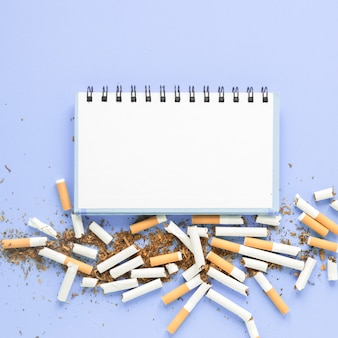 Vista superior cuaderno con montón de cigarros