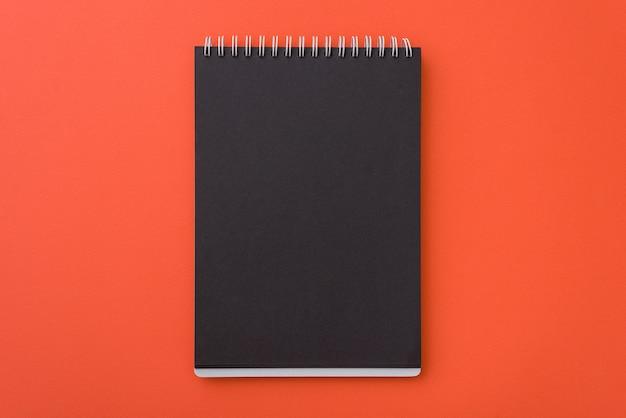 Vista superior del cuaderno negro en blanco espiral abierto l sobre fondo de escritorio naranja, lugar para el texto