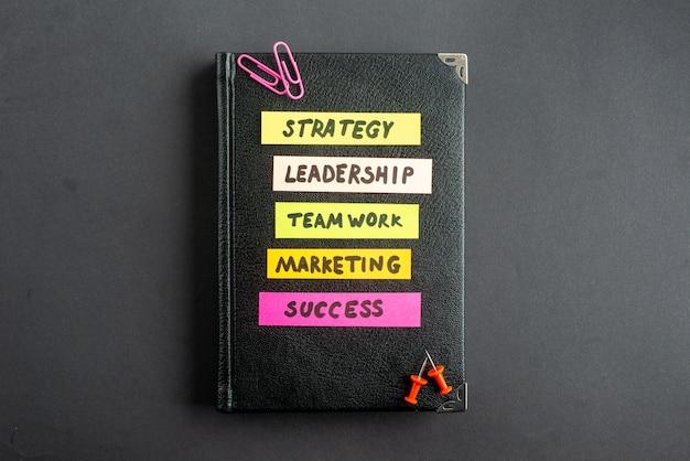 Vista superior cuaderno negro con notas comerciales en pegatinas sobre fondo oscuro estrategia trabajo de marketing empresarial trabajo en equipo liderazgo de oficina éxito laboral