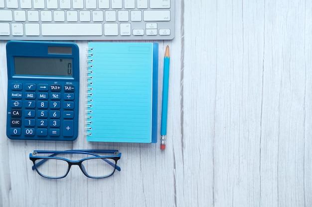 Vista superior del cuaderno de notas, calculadora, lápiz sobre fondo blanco.