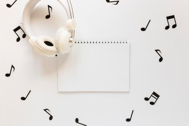 Vista superior del cuaderno de notas musicales y auriculares
