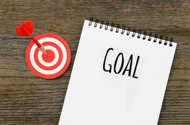 Vista superior del cuaderno con objetivo y objetivo con dardo