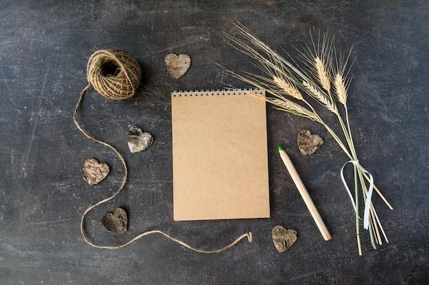 Vista superior del cuaderno de papel reciclado artesanal con manojo de espigas de trigo