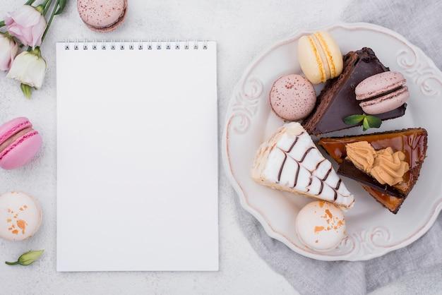 Vista superior del cuaderno con pastel en plato y macarons