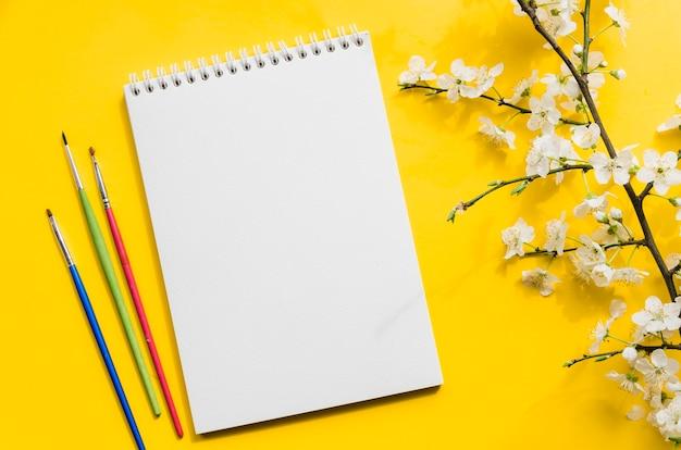 Vista superior cuaderno con rama de flores
