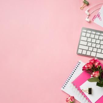 Vista superior del cuaderno y ramo de rosas en el escritorio con espacio de copia