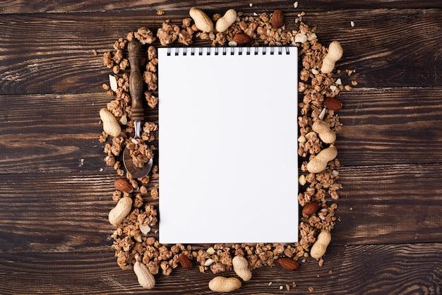 Vista superior del cuaderno rodeado de cereales para el desayuno con surtido de nueces