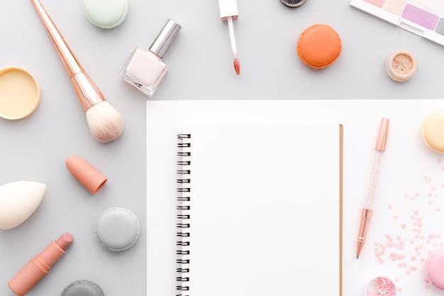 Vista superior cuaderno rodeado de maquillaje