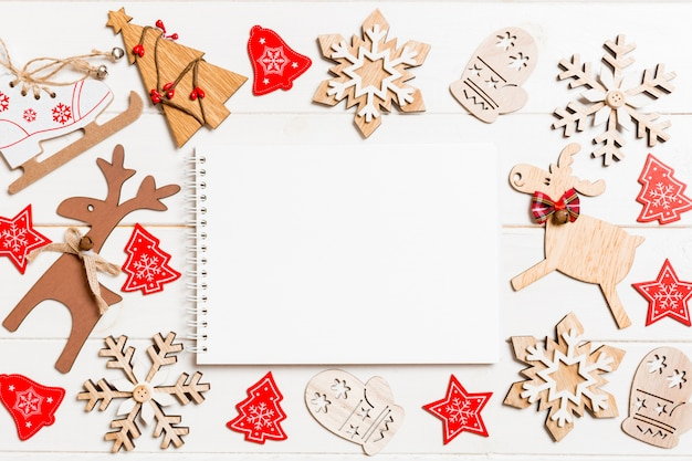 Vista superior del cuaderno sobre fondo de madera hecha de adornos navideños