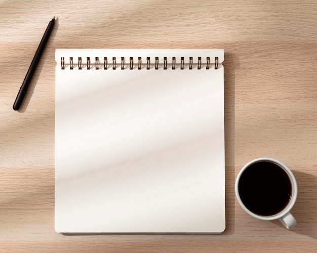 Vista superior del cuaderno con taza y bolígrafo