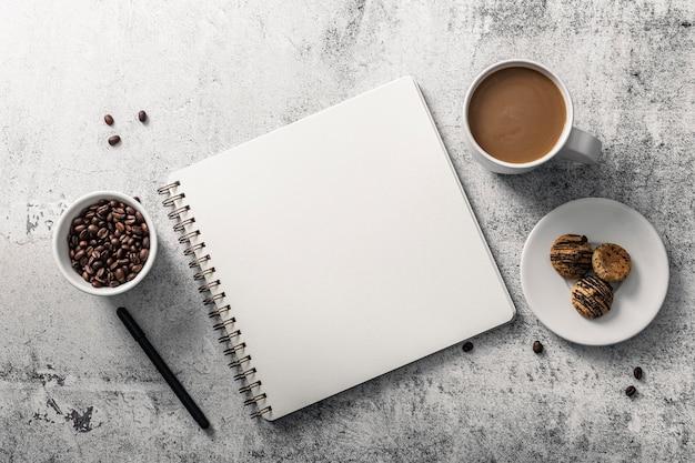 Vista superior del cuaderno con taza de café y galletas en la placa