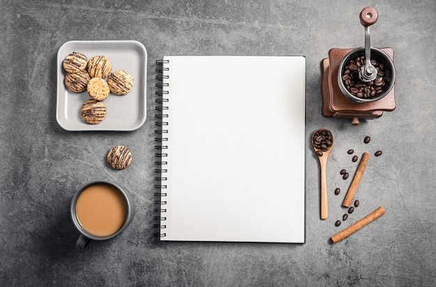 Vista superior del cuaderno con taza de café y molinillo