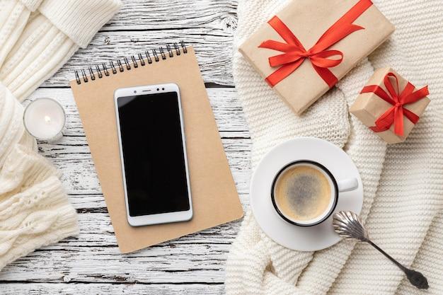 Vista superior del cuaderno con teléfono inteligente y taza de café