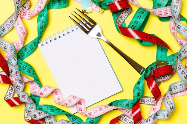 Vista superior del cuaderno con tenedor rodeado de coloridas cintas de medición en amarillo. copyspace con planificación de dieta