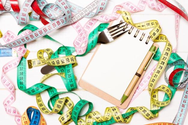 Vista superior del cuaderno con tenedor rodeado de coloridas cintas de medición en madera blanca. copyspace con planificación de dieta