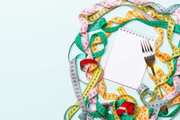 Vista superior del cuaderno con tenedor rodeado de coloridas cintas de medición sobre fondo azul.