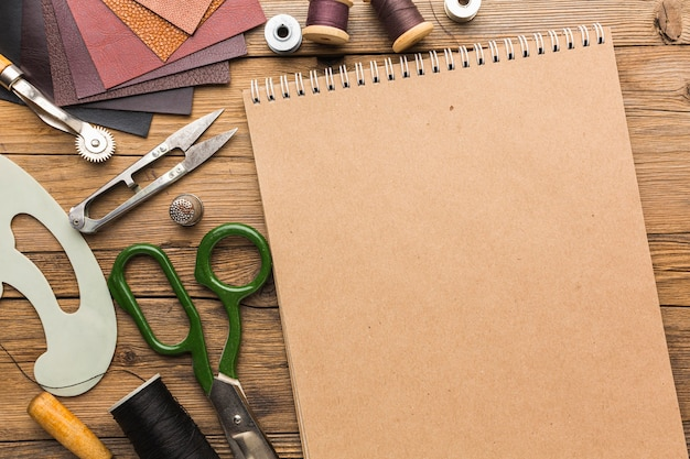 Vista superior del cuaderno con tijeras y cuero