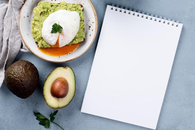 Vista superior del cuaderno con tostadas de aguacate en un plato y huevo escalfado en la parte superior