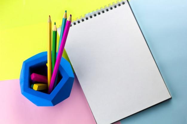 Vista superior del cuaderno de trabajo brillante con espacio de hoja vacía y lápices brillantes
