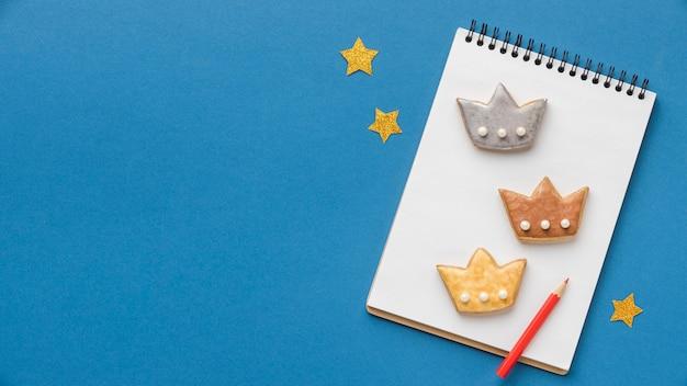 Vista superior del cuaderno con tres coronas y estrellas para el día de la epifanía