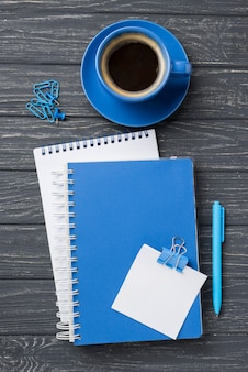 Vista superior de cuadernos en escritorio de madera con taza de café y bolígrafo