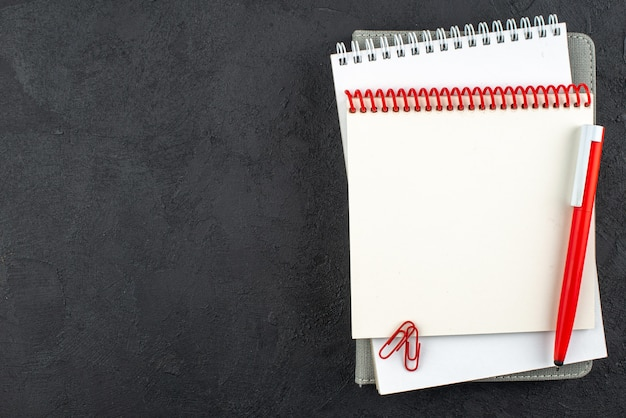Vista superior de cuadernos de espiral, clips de gemas de bolígrafo rojo sobre fondo oscuro