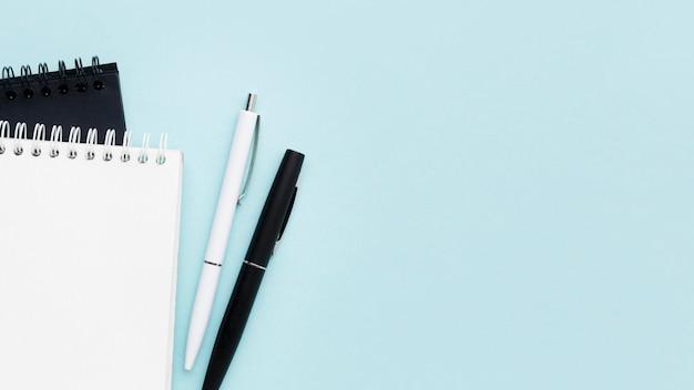 Vista superior de cuadernos y plumas