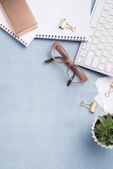 Vista superior de cuadernos con teclado y planta suculenta