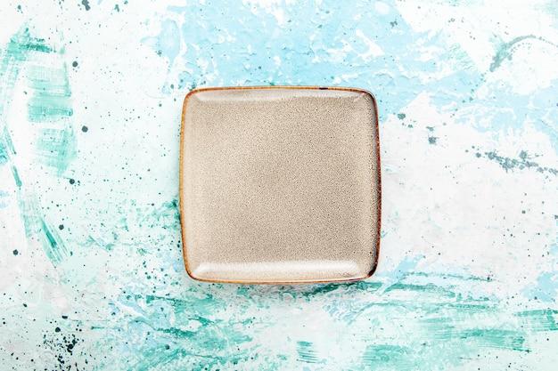 Vista superior cuadrado de placa marrón vacío formado sobre fondo azul claro cubiertos de plato de comida de cocina