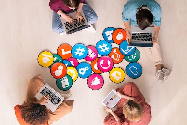 Vista superior de cuatro jóvenes amistosos en ropa casual sentados junto a papeles multicolores con iconos en el suelo y usando dispositivos móviles