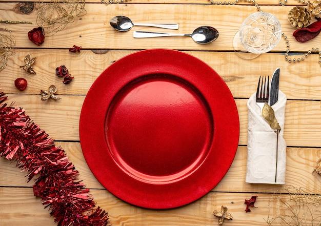 Vista superior de cubiertos y platos sobre fondo de madera festivo