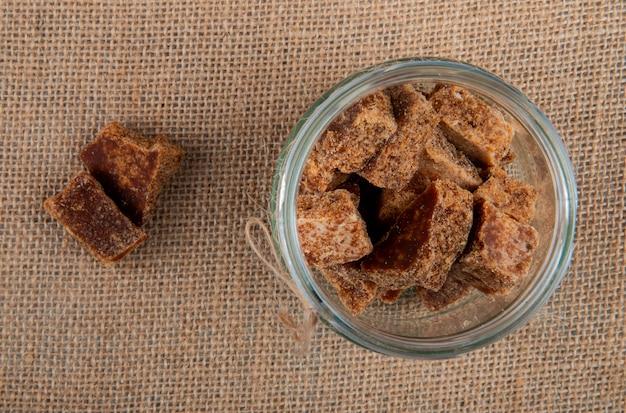 Vista superior de cubitos de azúcar de palma en un frasco de vidrio sobre fondo de textura de tela de saco