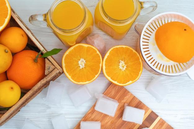 Vista superior de cubitos de hielo sobre tabla para cortar madera delante de vasos de jugo de naranja