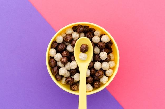 Vista superior cuchara amarilla con tazón de cereales de chocolate