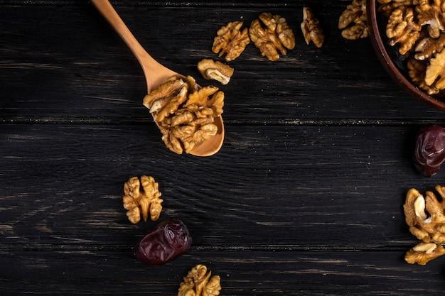 Vista superior de una cuchara de madera con nueces y frutas dulces de dátiles secos en madera