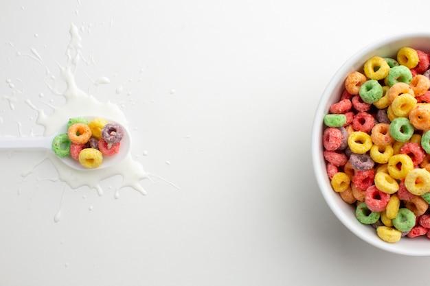 Vista superior cuchara de plástico y tazón de cereal