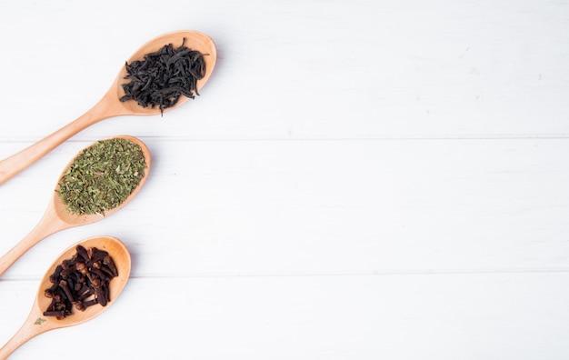 Vista superior de cucharas de madera con especias y hierbas, hojas secas de té negro, especias de clavo y menta seca en madera blanca con espacio de copia