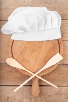 Vista superior de cucharas de madera y gorro de cocinero