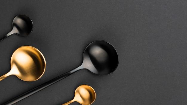 Vista superior de cucharas negras y doradas con espacio de copia