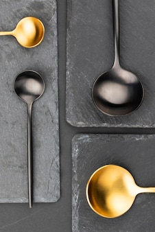 Vista superior de cucharas negras y doradas en pizarra