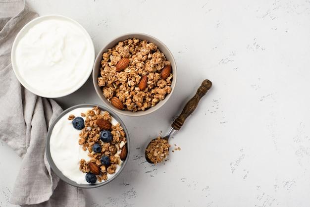 Vista superior de cuencos con cereales para el desayuno y yogurt