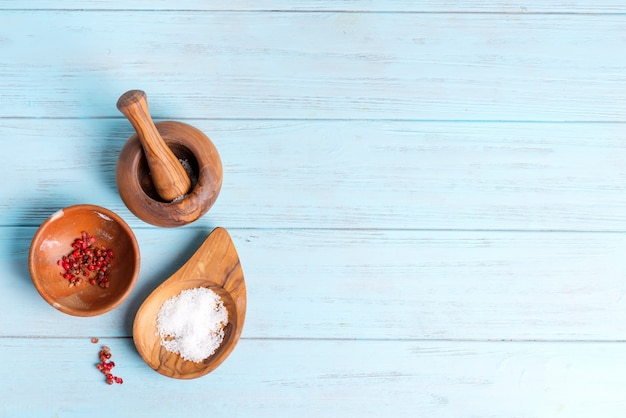 Vista superior de cuencos de madera con sal natural y condimentos.